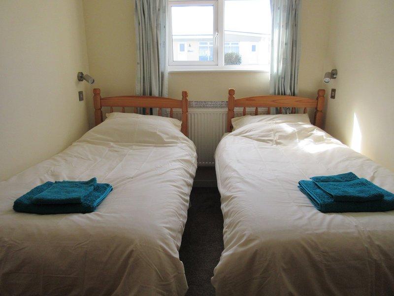 habitación con dos camas hechas con ropa de cama y toallas incluidas
