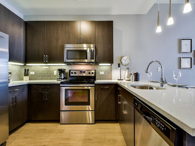 The kitchen has contemporary dark wood cabinets and stainless steel appliances.