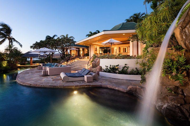 Palatial estate home at twilight with private pool, waterfall, and jacuzzi grotto.