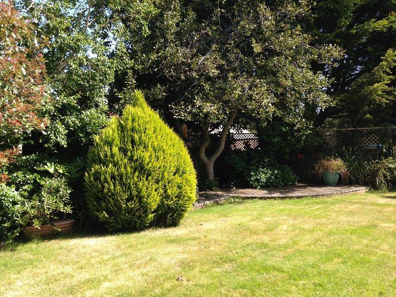Garten hat einen Terrassenbereich an einem sonnigen Standort, reifes Strauchwerk sorgt für Abgeschiedenheit