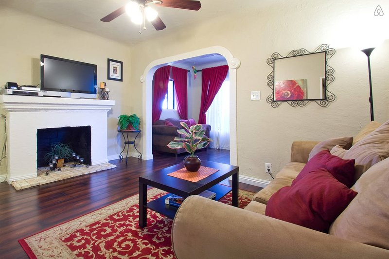 Living room with sofa sleeper, TV w/dish, hardwood floors.