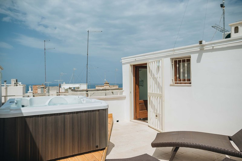 Roof terrace: Jacuzzi and sunbeds with sea water view