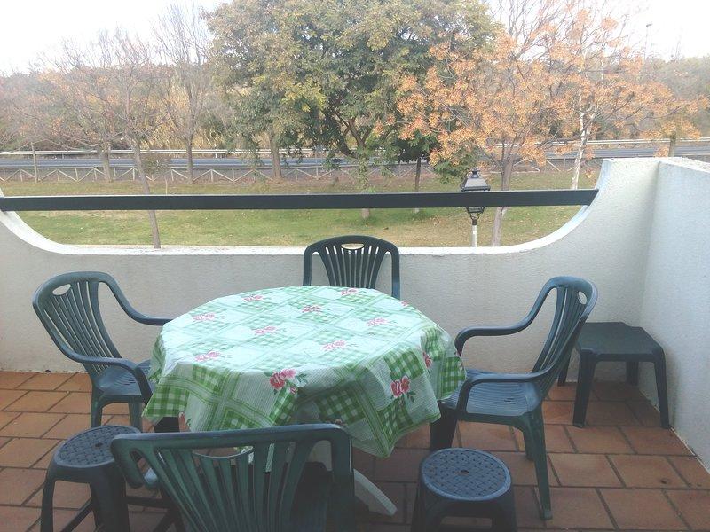 Terrasse avec table et chaises. Jardin devant.