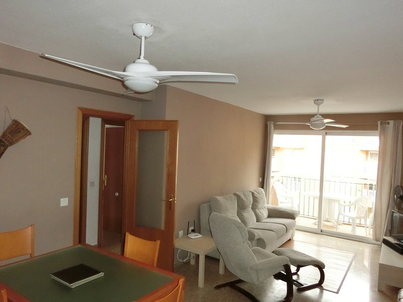 the lounge and dining area with two ceiling fans, plasma tv and dvd player