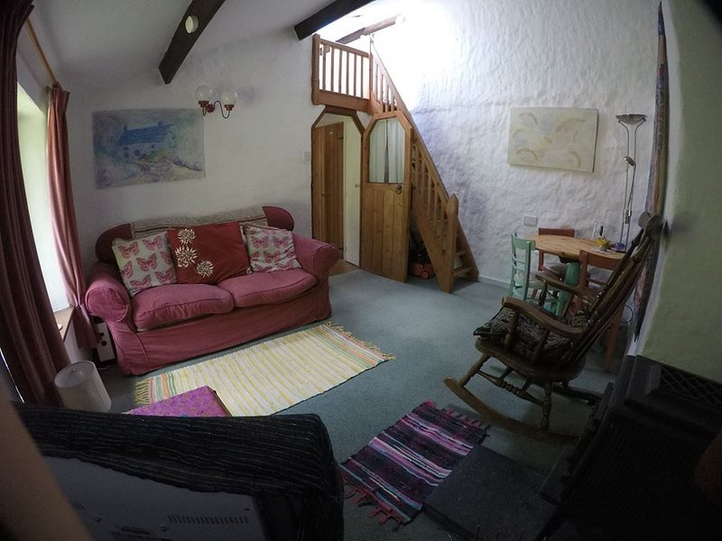 View of living room showing settee+stairs upt to double sleeping loft - taken with a fish eye lense.