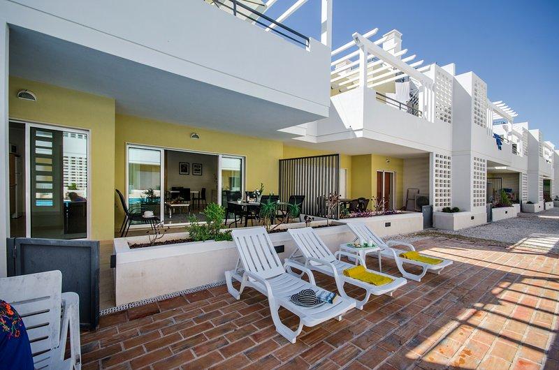 De kleine poort leidt naar de terrassen bij het zwembad en ligstoelen