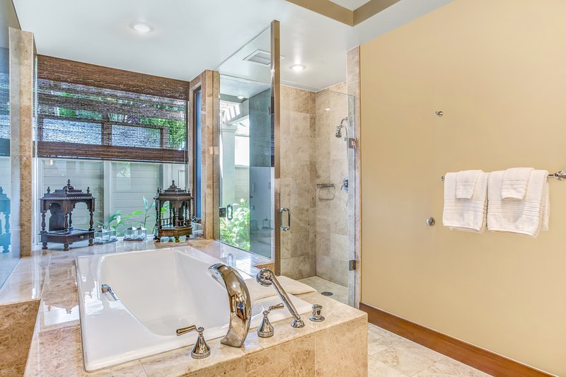 Master Bathroom with Luxurious Soaking Tub and Separate Tiled Shower that Opens into Private Courtyard with Outdoor Shower