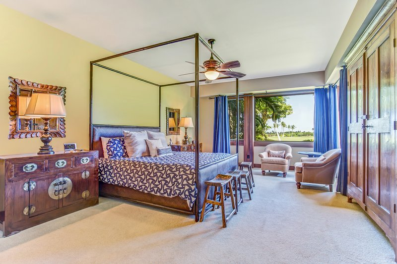 Spacious Master Bedroom with Flat-Screen TV, Sitting Area and Large Windows Looking Out Over Golf Course
