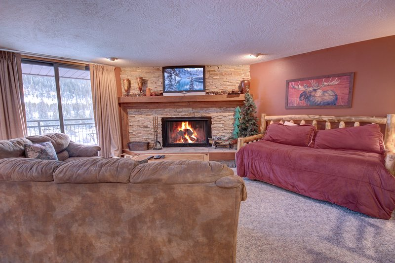 Living room has a fireplace to cozy up to after a long day of hiking or hitting the slopes.