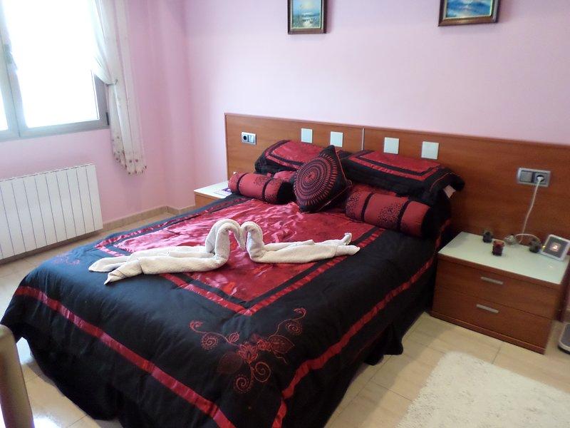 El dormitorio principal, con cama extragrande, baño privado y TV de pantalla plana.