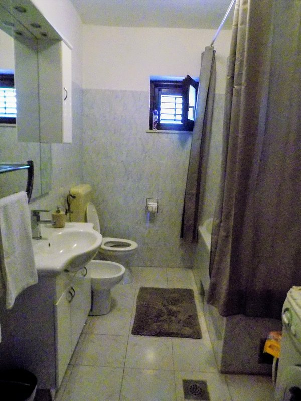 Bathroom with bath and shower, toilet and bidet, water heater, washing machine and hairdryer