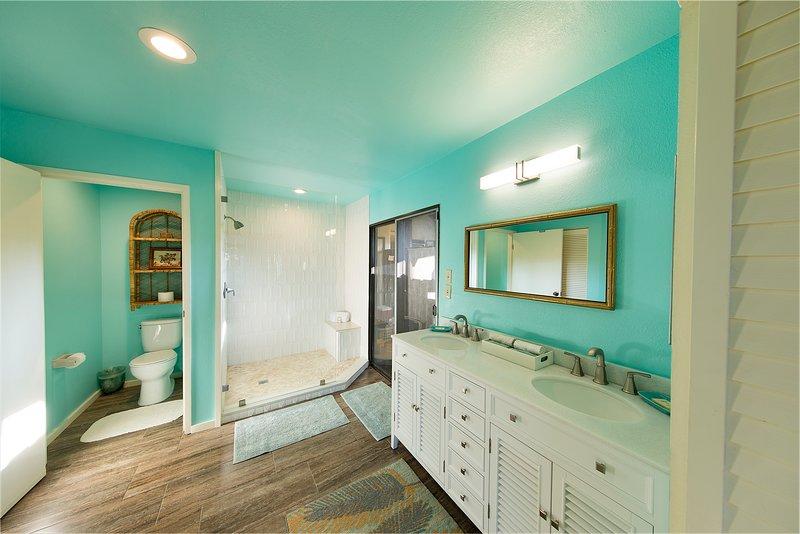Amplio baño principal tiene inodoro, ducha con banco, tocador doble y lavadero