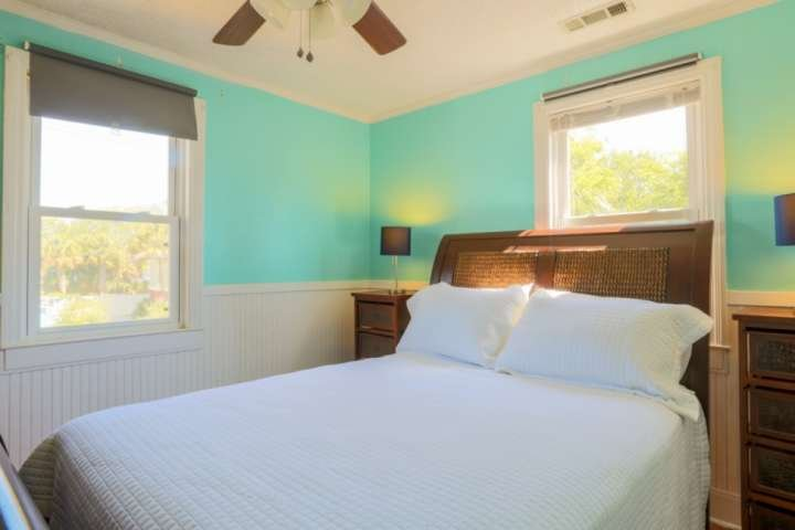 The second bedroom in the home features a queen bed, nightstands with reading lamps and a ceiling fan.