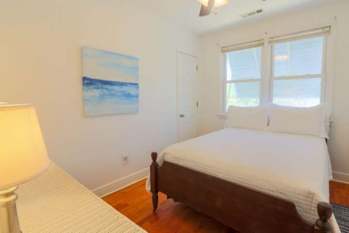 The third bedroom in the home features a full-sized bed with a dresser, ceiling fan and hardwood floors.