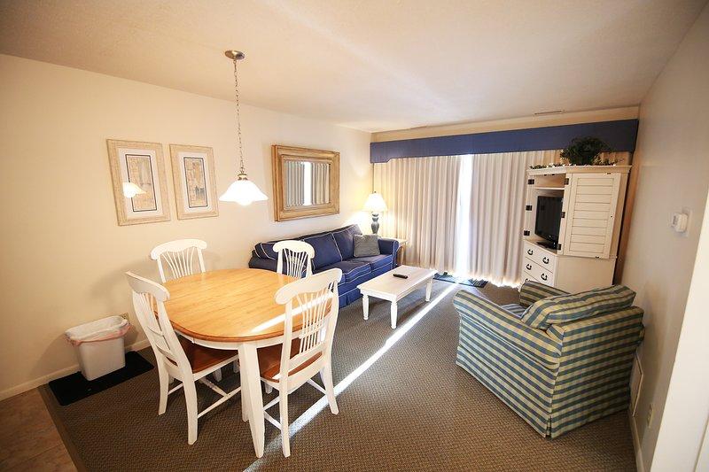 Prachtig goed verlichte woonkamer, die zich opent naar een groot dek.