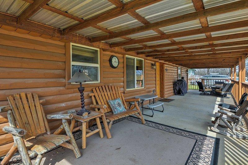 Descansar y relajarse en el amplio porche, con una parrilla de gas y mesa de comedor.