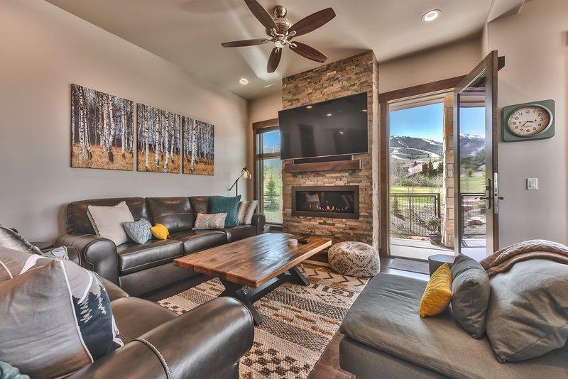Ameublement contemporain et confortable, comprenant un canapé-lit queen-size, une Smart TV de 65 pouces, une Apple TV, une cheminée à gaz et un accès à la terrasse