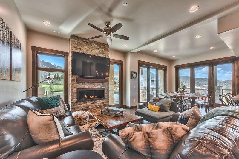 Grande salle avec salon, salle à manger et cuisine avec de beaux planchers de bois franc à travers