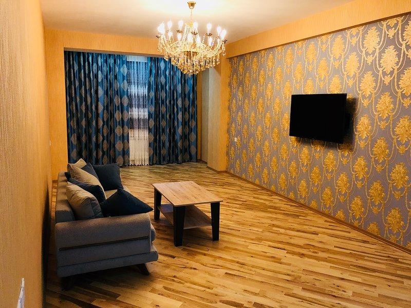Moderno soggiorno con grande schermo, lampadario e divano.