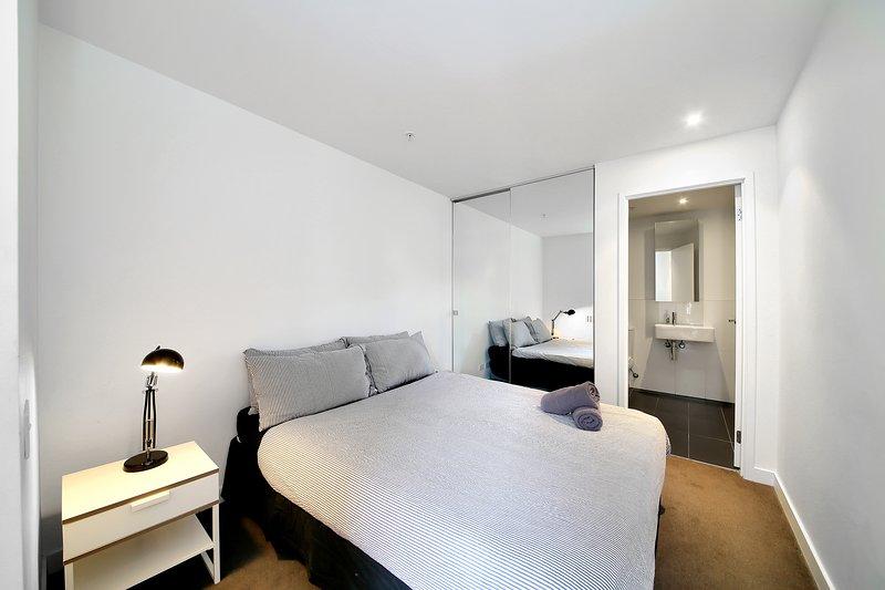 Una camera da letto con un letto queen size e soffici cuscini.
