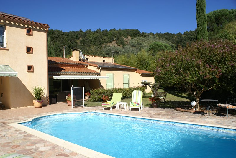 Pool, outside area and house, nestling in a green valley