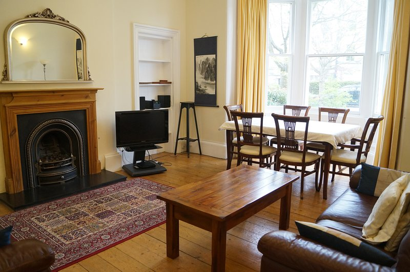 Large living room with seating and dining area and lots of period features.