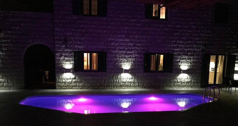 Pool lights reflection on villa wall