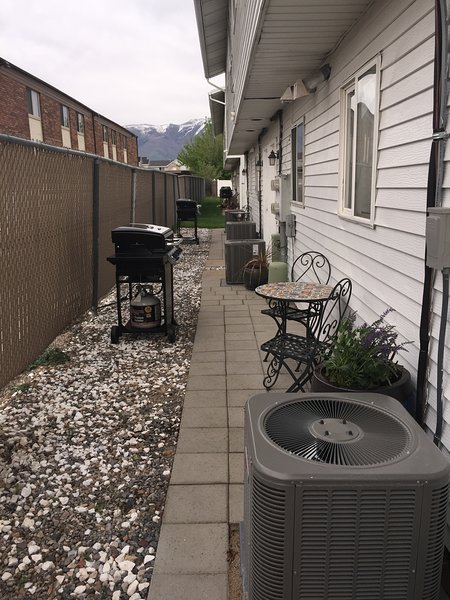 The back patio is a shared common area with tables, chairs and two four burner charbroil gas grills.