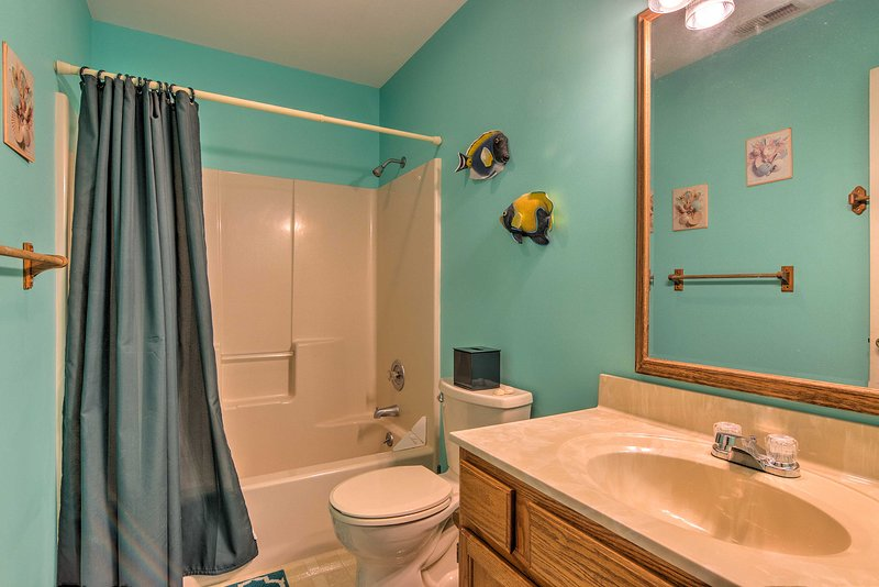 The full bathroom is equipped with a shower/tub combo.