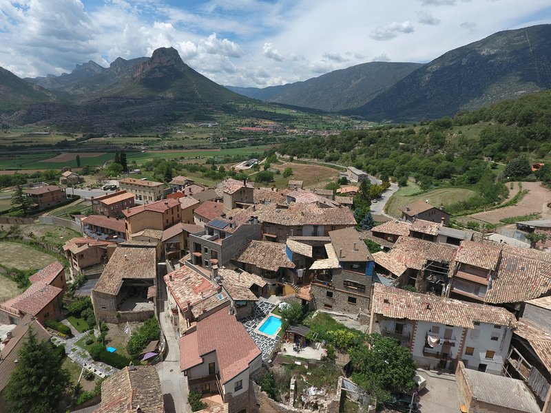 Drone view of house and village of Figols - with Santa Fe in the background