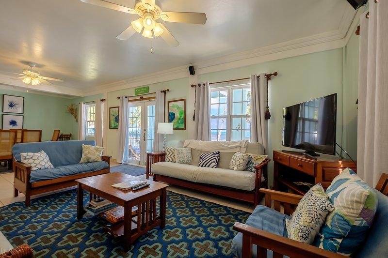 Accogliente, caldo e colorato soggiorno. Francese porte conducono direttamente alla veranda e spiaggia oltre.