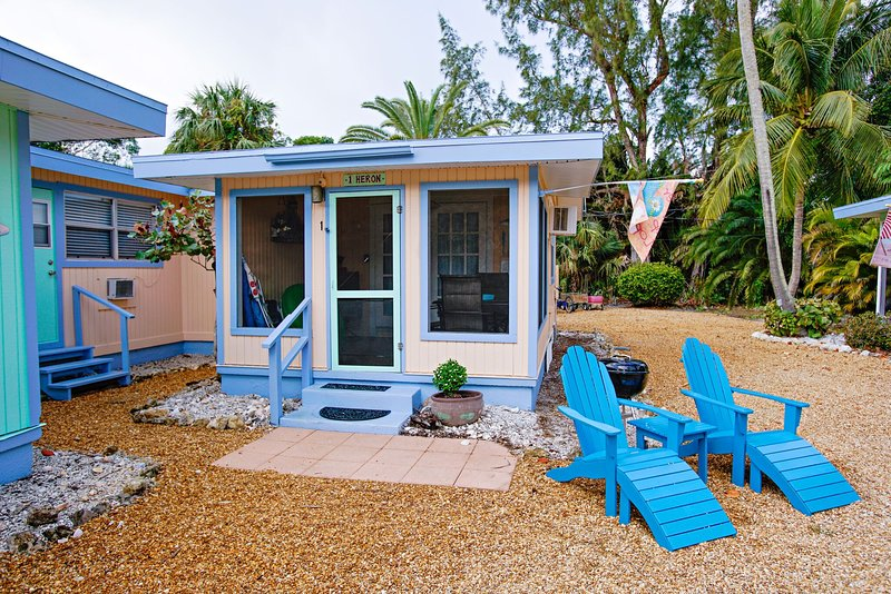 Heron Cottage exterior with screened lanai and adirondack chairs and grill.