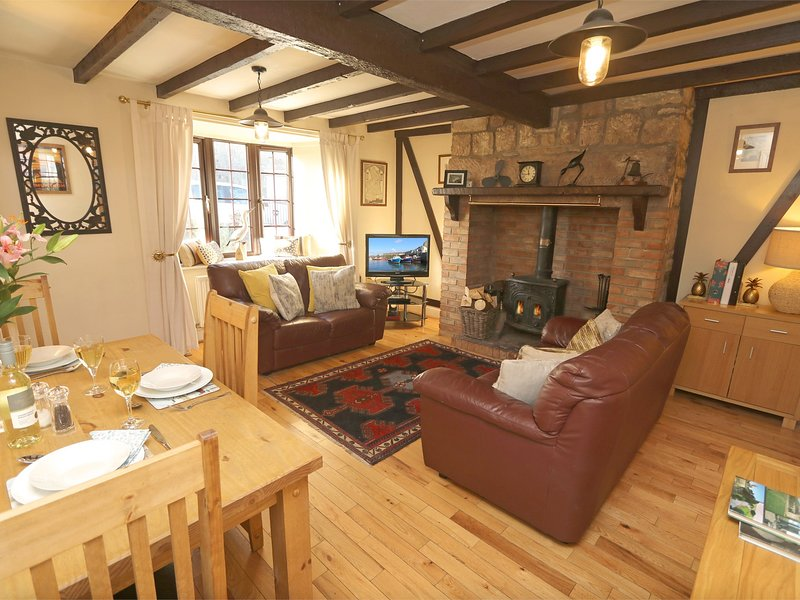 Lounge with beams and a wood burning stove