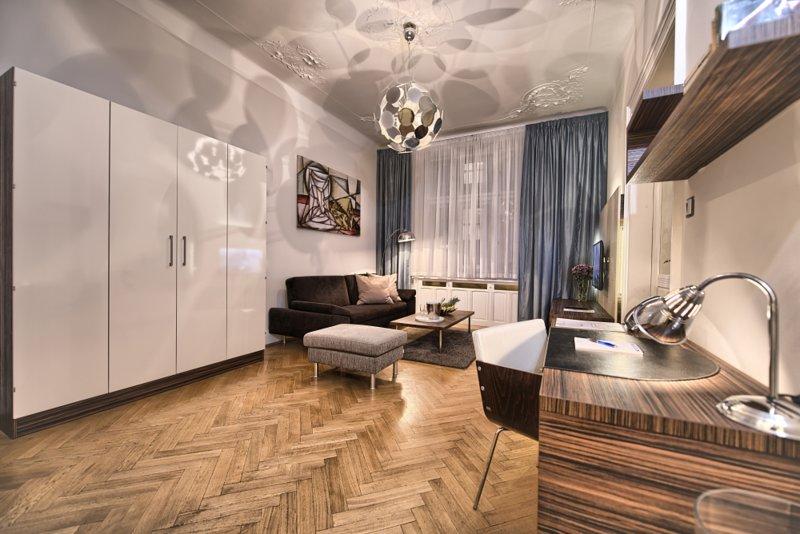 Amplia sala de estar con un cómodo sofá, TV de pantalla plana y escritorio.