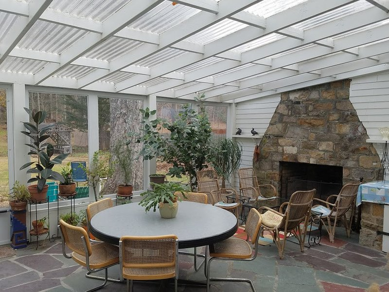 The 3-season room with fireplace, table and lounge seating and vistas onto the lawns and gardens.
