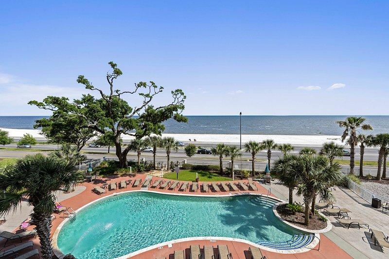 Uitzicht op het zwembad en het strand vanaf het balkon van Trade Winds condominium