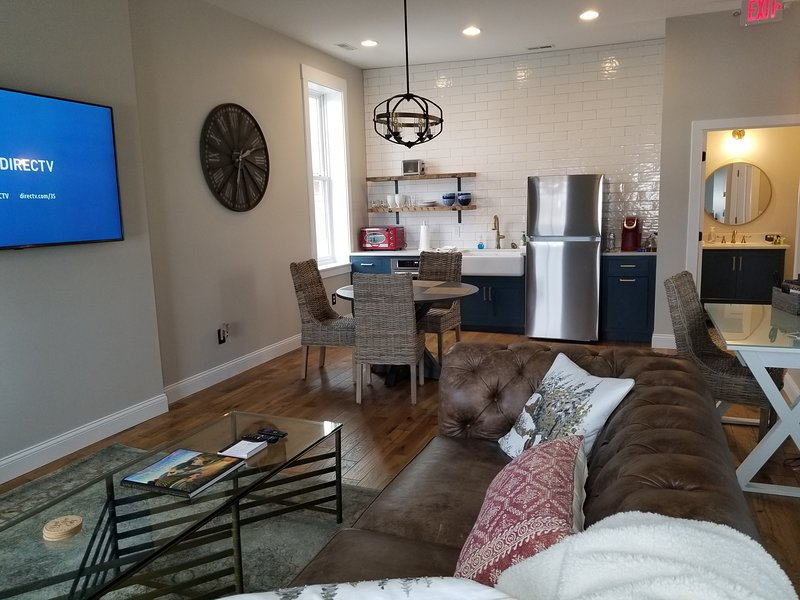 Leather couch, 65' TV, dining table, desk, kitchen, and bathroom in large open loft style living.