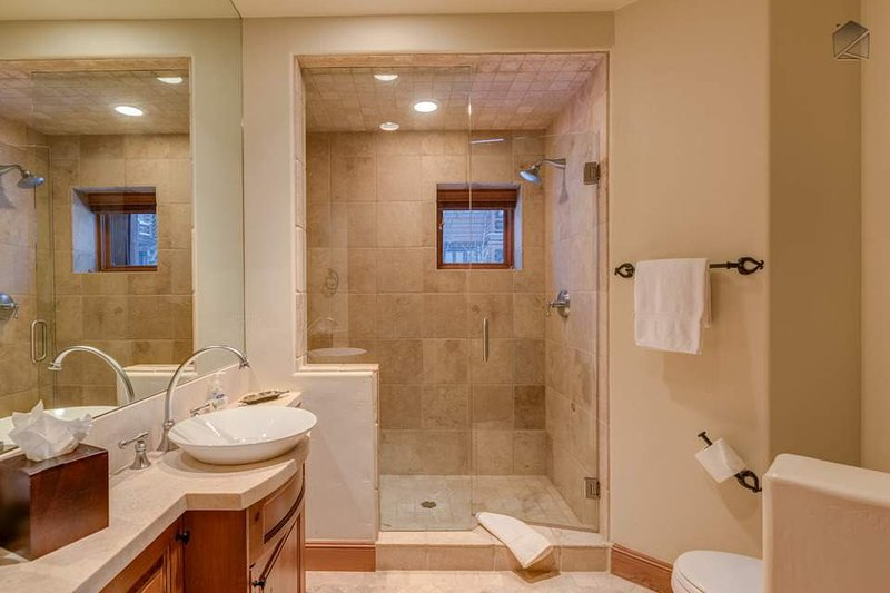 The second guest ensuite bathroom has an elegant walk-in shower and modern sink. This bathroom is available to the living spaces as well.
