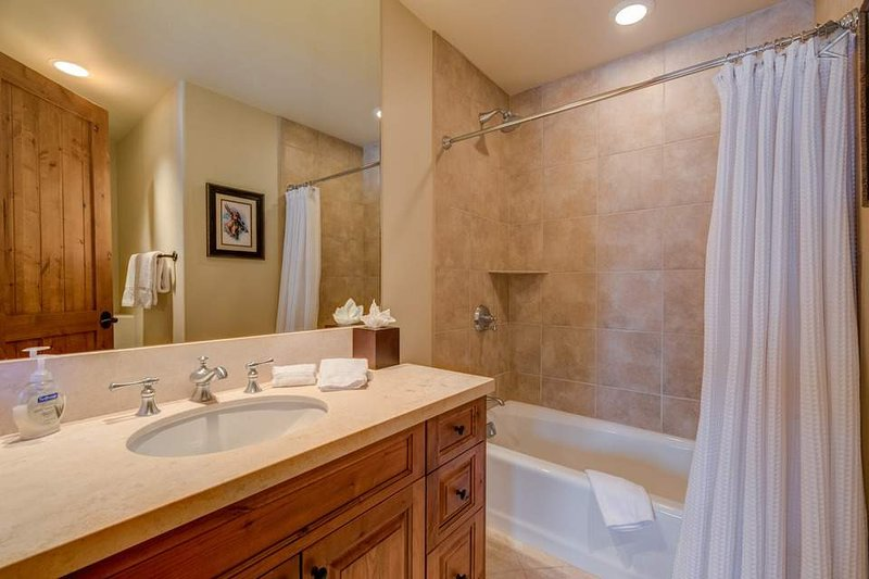 The third guest ensuite bathroom has a shower/tub combination and a single sink.