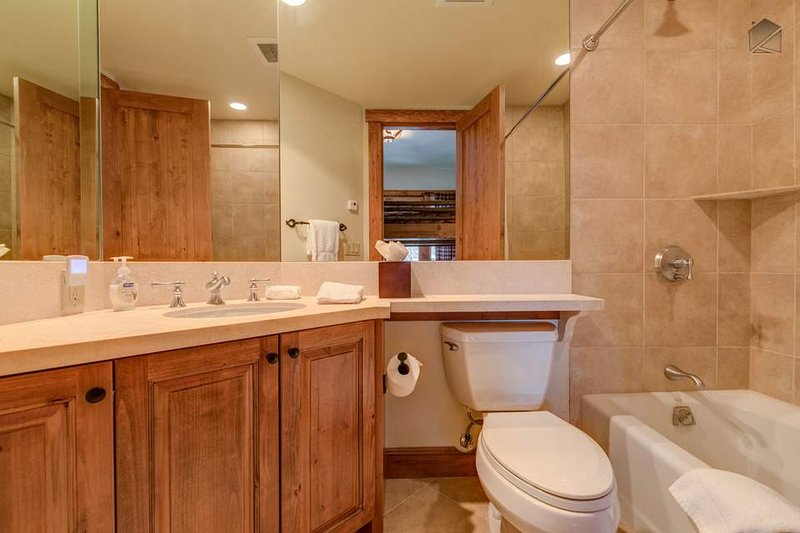 The bunk room's attached ensuite has a shower/tub combination and a large corner mirror.