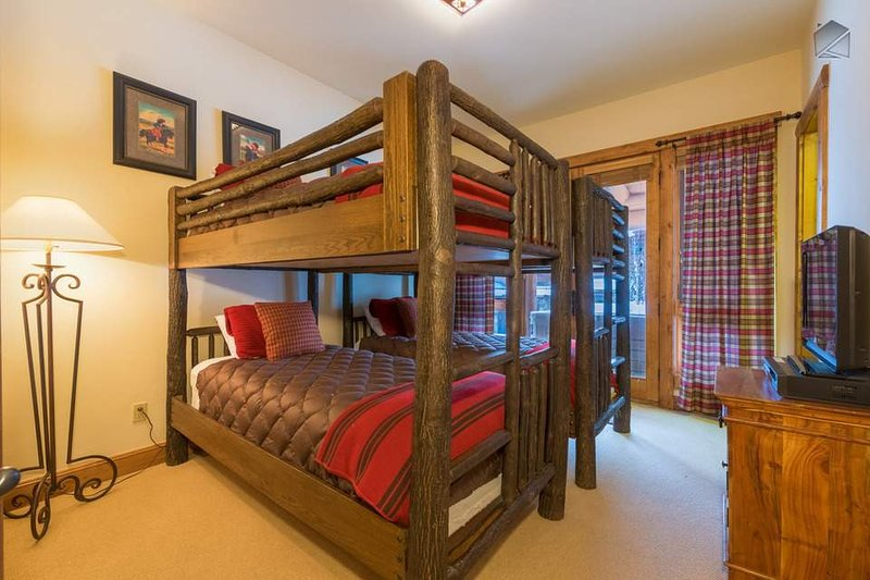 The cozy bunk room has two sets of bunks, a TV, and an attached ensuite bathroom.