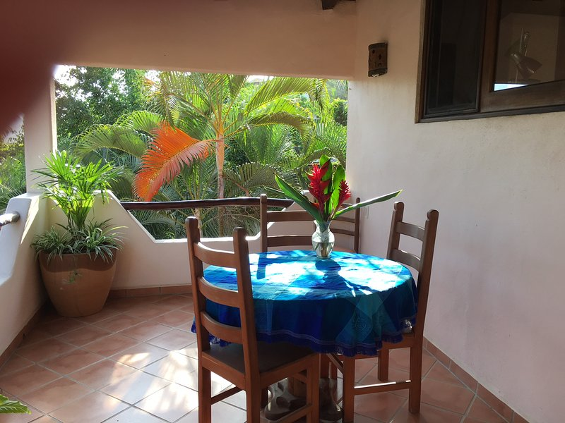 Dining area on the back balcony overlooking the garden
