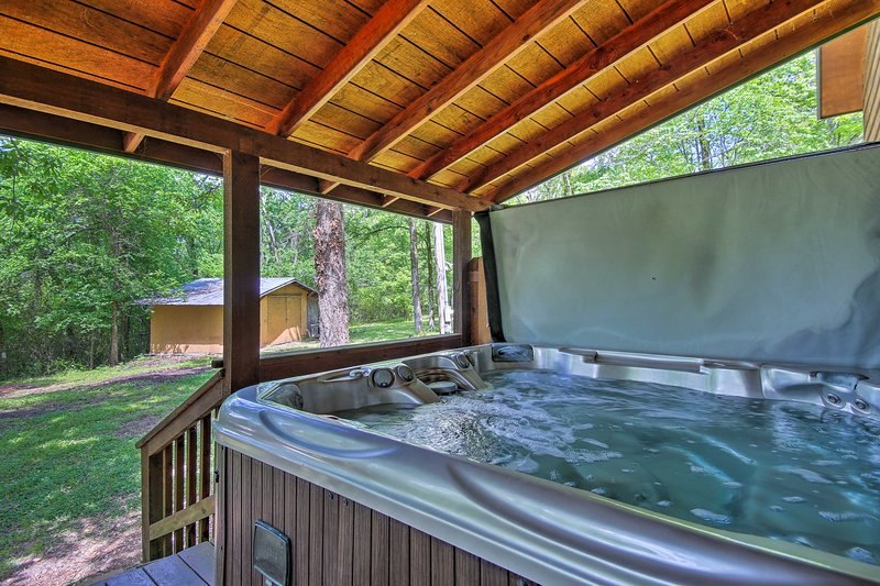 This cozy home has a private hot tub & is just 5 minutes from the lake!