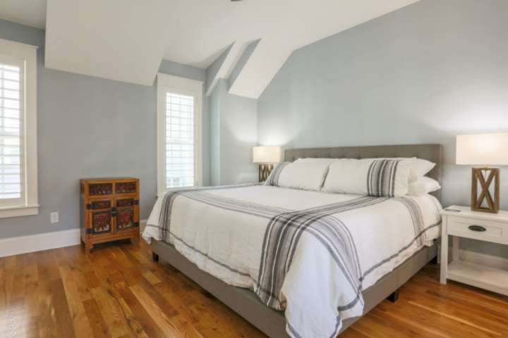 The upstairs master suite has a king bed, hardwood floors and nightstands with reading lamps.