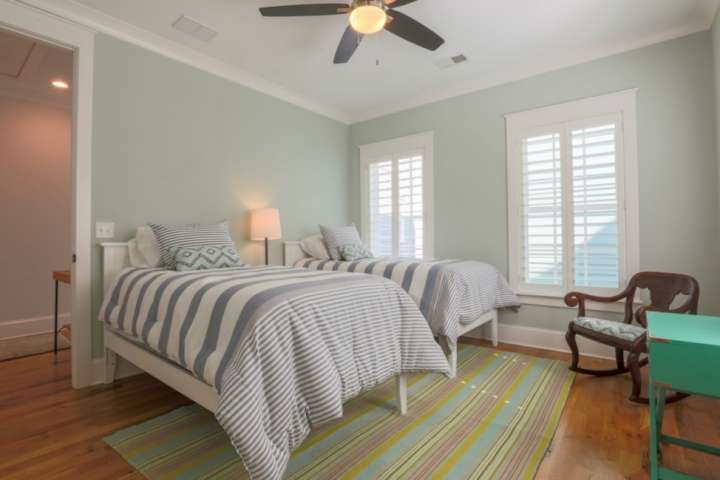 The second bedroom on the second floor features two twin beds, a ceiling fan and rocking chair.