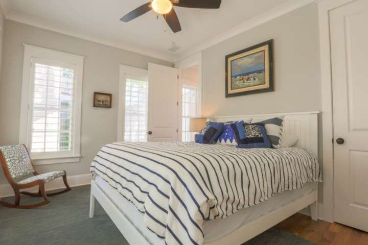 This bedroom features a queen bed, ceiling fan, rocking chair and nightstand with reading lamp.