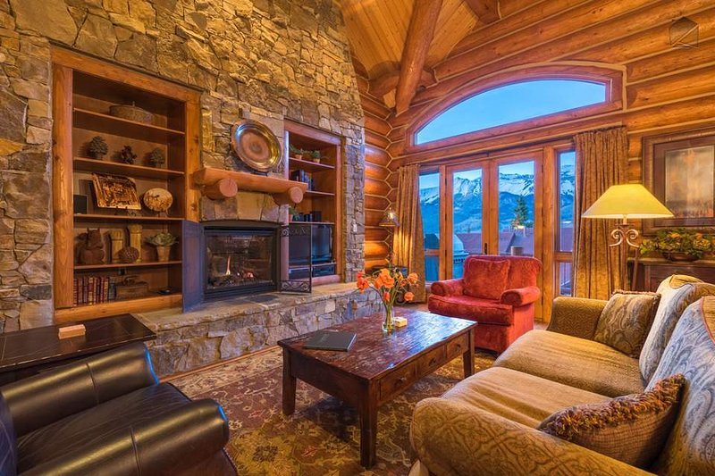 The main living area has a cozy fireplace built into the massive stone wall.