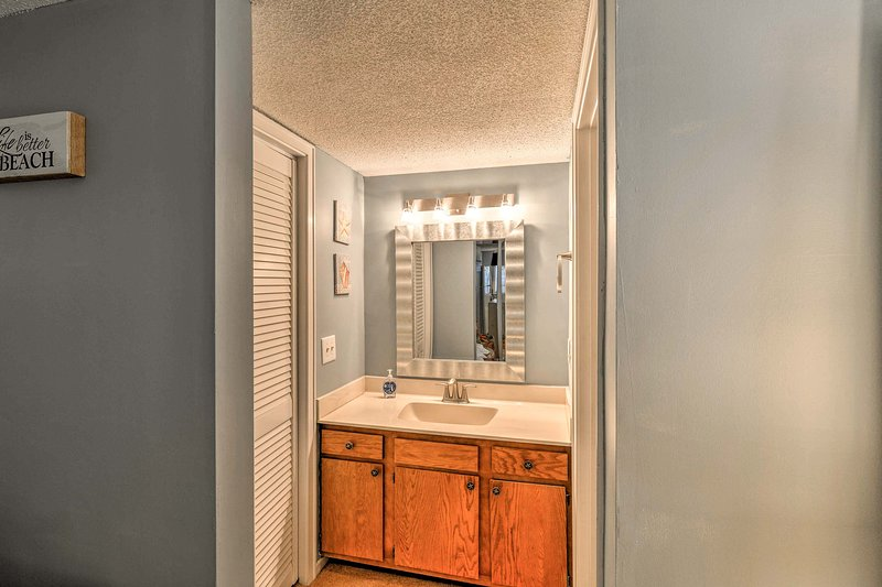 This full en-suite bathroom features a mirrored vanity and tub/shower combo.