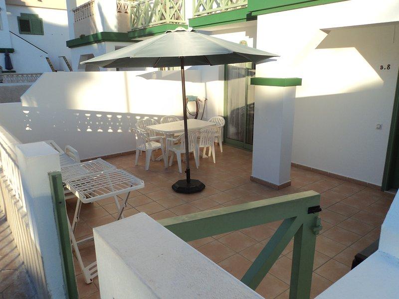 Patio avec table, chaises, parasol et chaises longues.