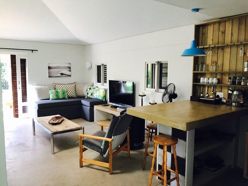 vie spacieux plan ouvert / salle à manger / cuisine avec une grande télévision à écran plat et plein DSTV et un lecteur DVD.